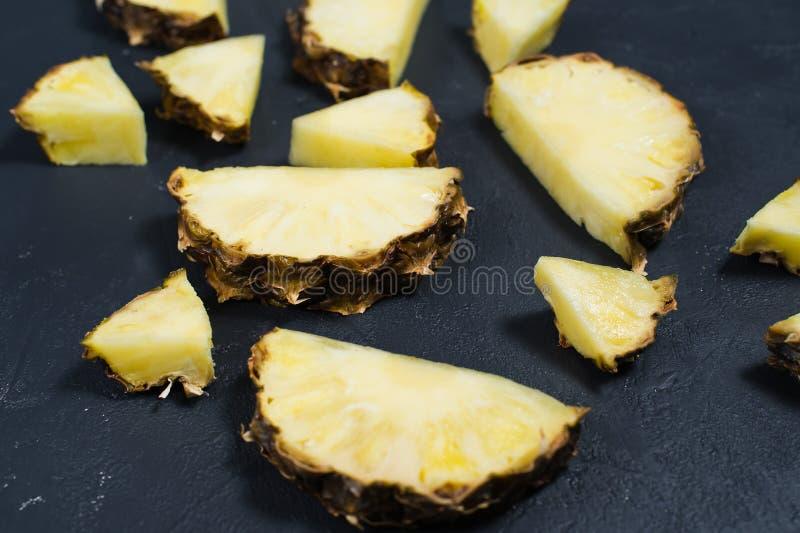 Fette dell'ananas su fondo nero con spazio per testo fotografia stock libera da diritti