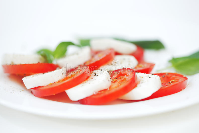 Fette della mozzarella e del pomodoro su una zolla fotografia stock