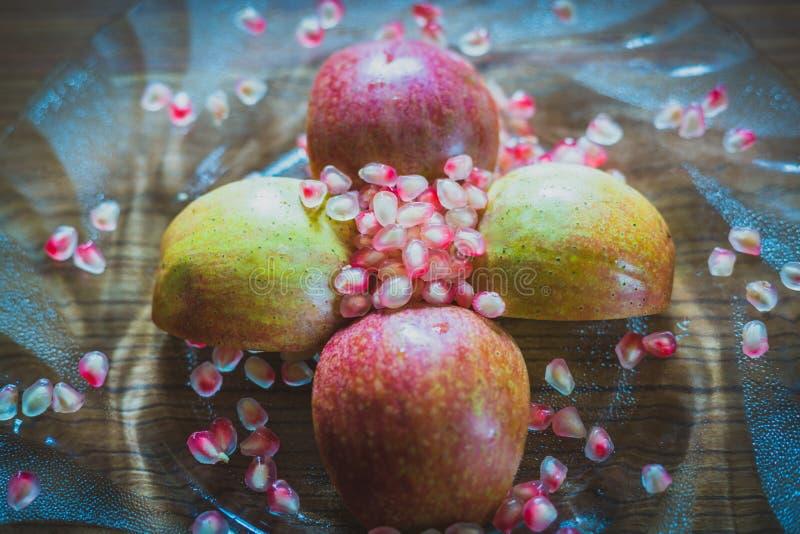 Fette di Apple e semi freschi del melograno immagine stock