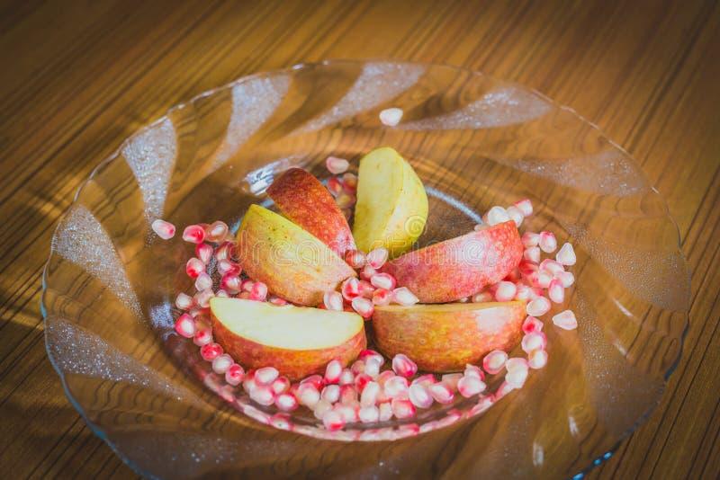 Fette di Apple e semi freschi del melograno immagini stock