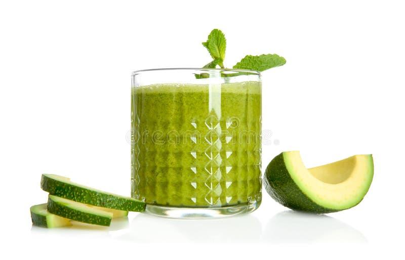 Fette di avocado e vetro maturi di frullato saporito su fondo bianco immagine stock libera da diritti