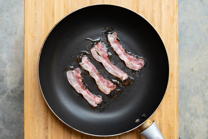 Fette di bacon fritto fresco in una pentola immagine stock