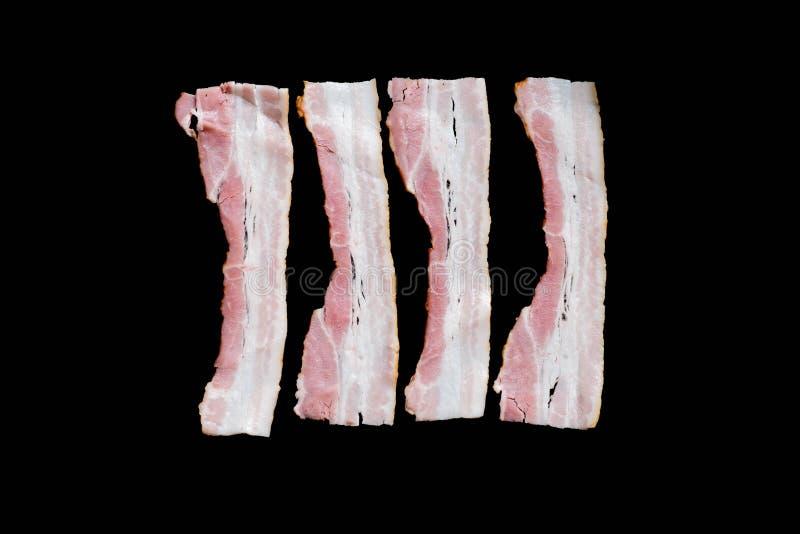 Fette di bacon fritto fresco in una pentola su un fondo nero immagini stock libere da diritti
