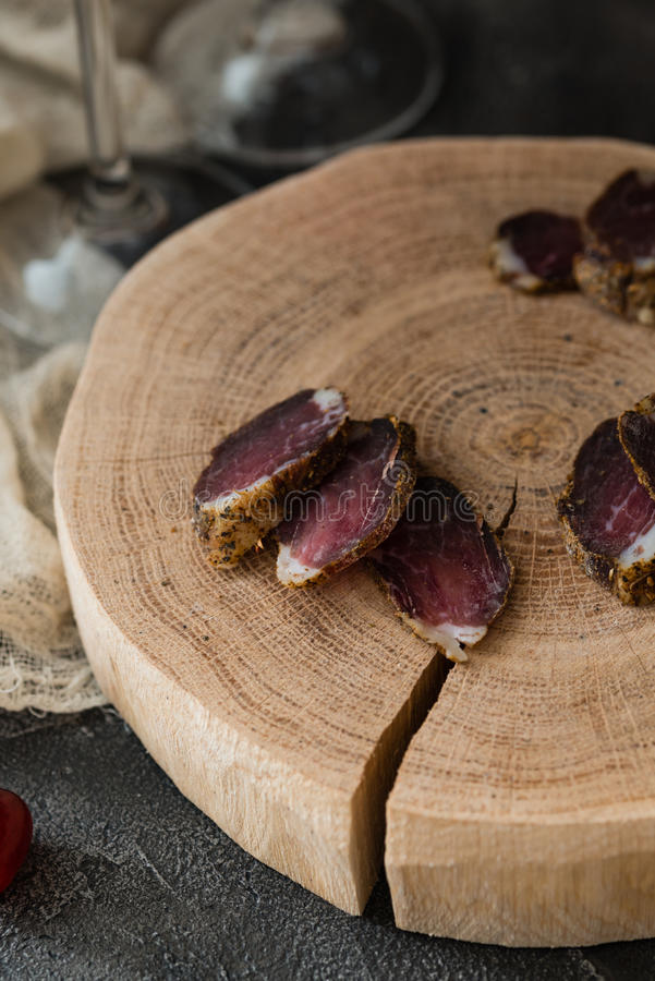 Fette di carne secca sul taglio di legno e di due gambe di vetro su fondo scuro immagini stock