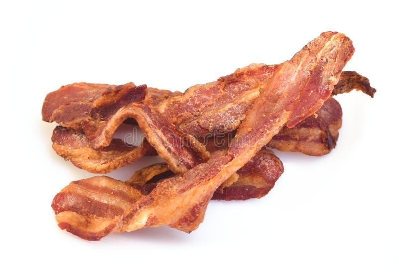 Fette di lardo croccanti del bacon isolate contro un fondo bianco fotografia stock