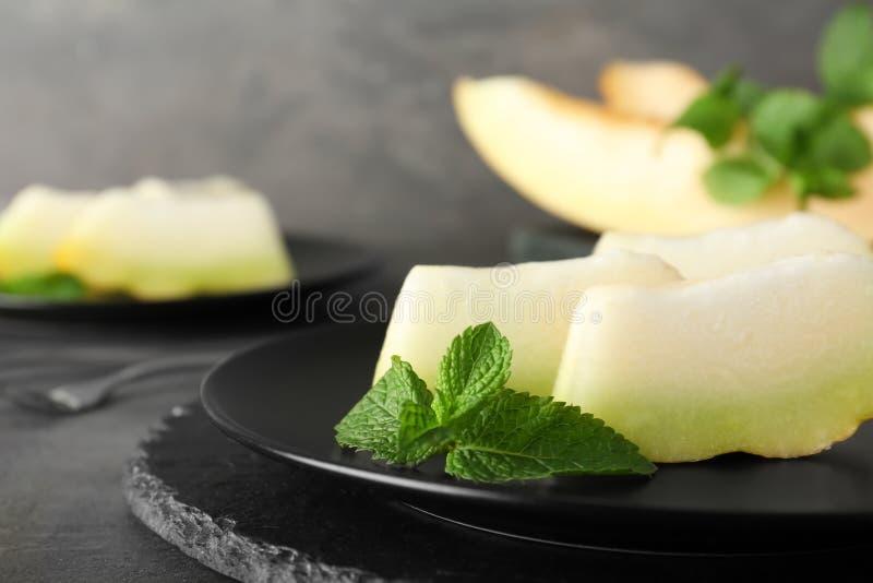 Fette di melone maturo fresco sul piatto immagine stock