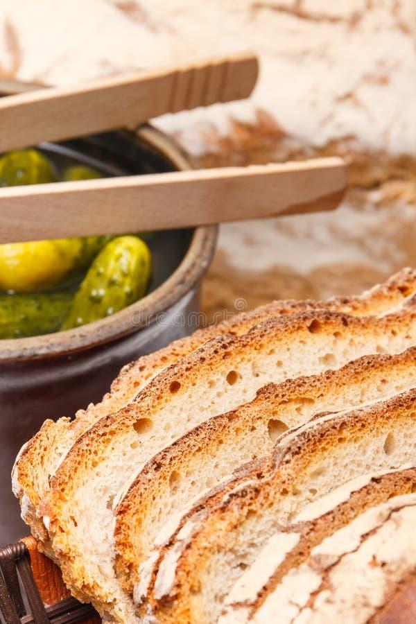Fette di pagnotta al forno fresca di segale o pane integrale e cetrioli marinati in vaso di argilla fotografia stock