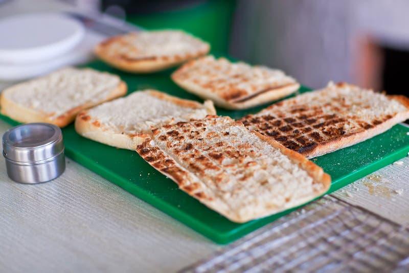 Fette di pane arrostite per il panini sul supporto verde fotografia stock