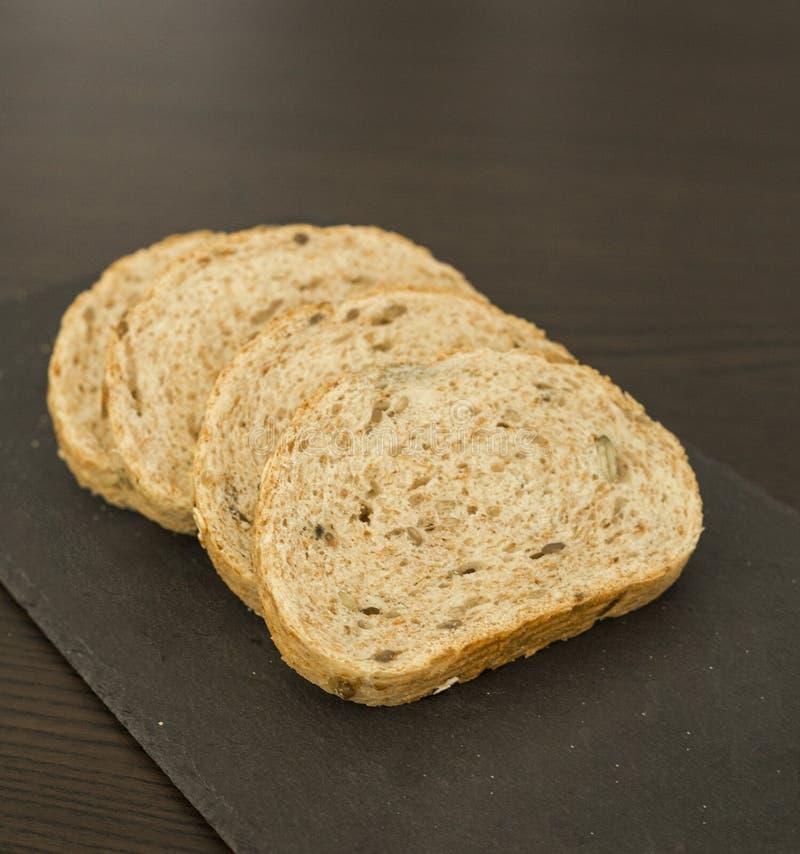 Fette di pane casalingo del multigrain sul bordo nero dell'ardesia fotografie stock libere da diritti
