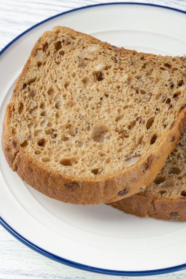 Fette di pane del grano con la muffa Su un piatto bianco con una banda blu Su una tabella di legno fotografia stock