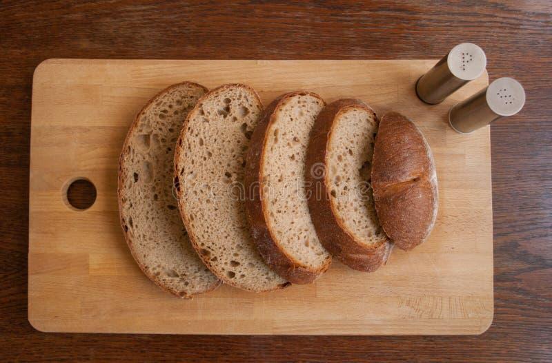 Fette di pane saporito disposte sul tagliere di legno fotografia stock