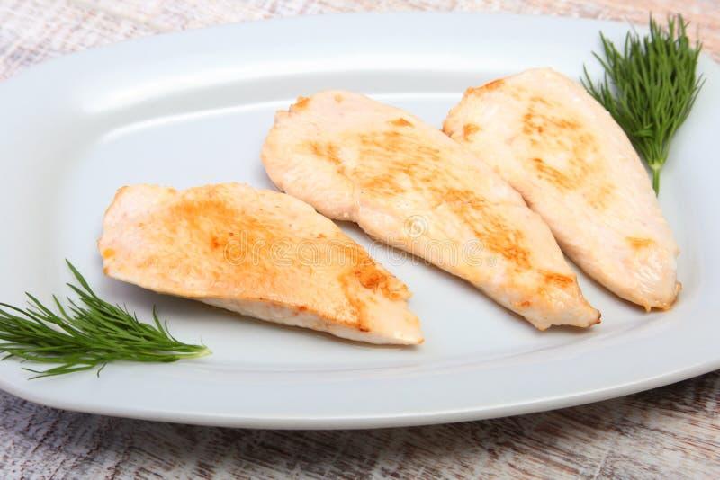 Fette di petto di pollo e di pomodoro arrostiti sul piatto bianco immagini stock
