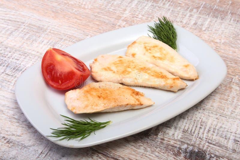 Fette di petto di pollo e di pomodoro arrostiti sul piatto bianco fotografia stock libera da diritti