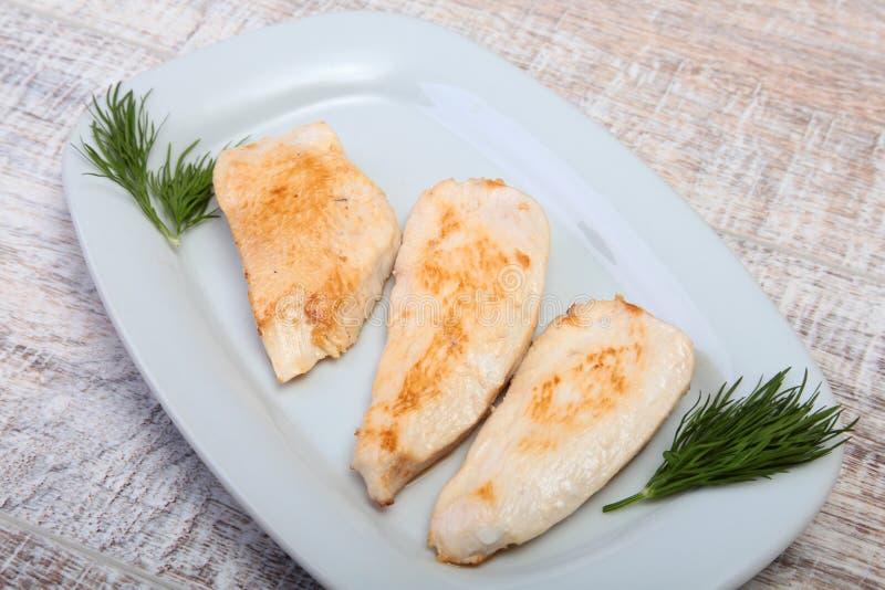 Fette di petto di pollo e di pomodoro arrostiti sul piatto bianco fotografia stock