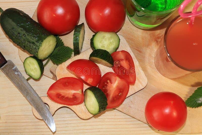 Fette di pomodori e di primo piano rossi succosi dei cetrioli sulla tavola immagini stock libere da diritti