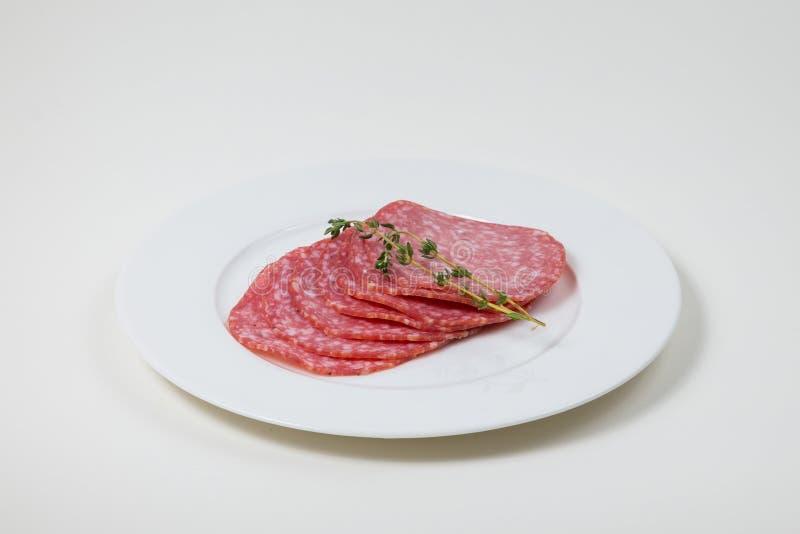 Fette di salame su un piatto bianco su un fondo bianco isolato immagine stock libera da diritti