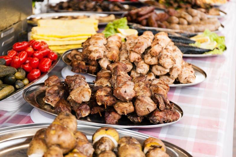 Fette di taglio della carne suina del manzo e del BBQ carne dell'arrosto sugli spiedi su fuoco aperto fotografie stock