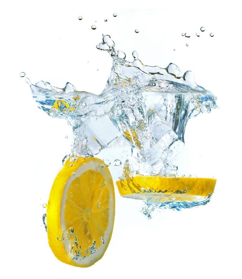 Fette e cubetti di ghiaccio del limone che spruzzano acqua fotografia stock libera da diritti