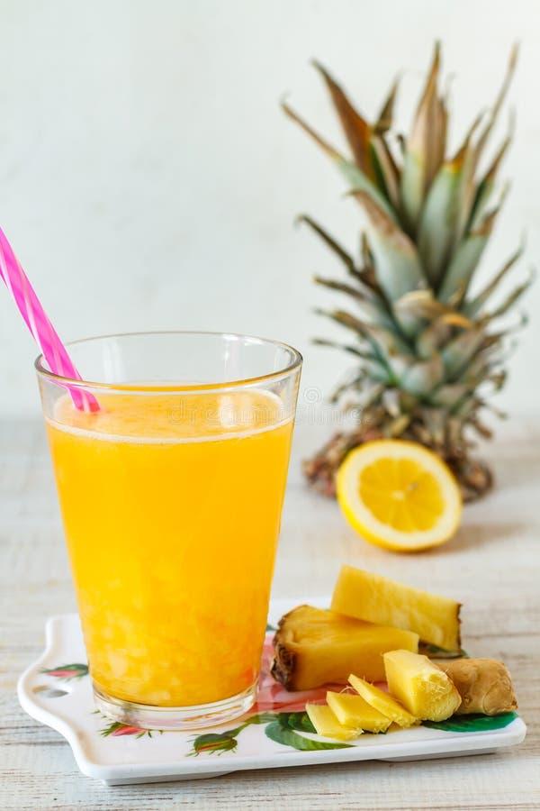 Fette e succo dell'ananas in cristalleria sulla tavola di legno fotografie stock