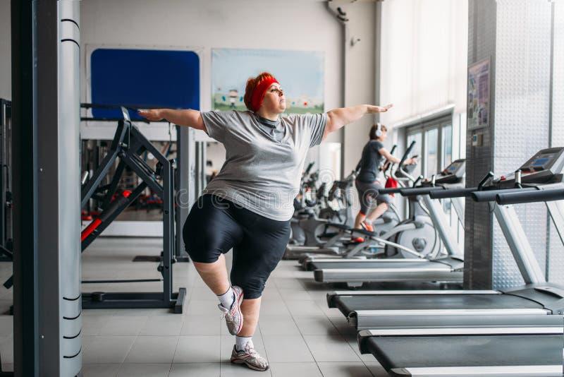 Fette Frau, die Balancenübung in der Turnhalle tut lizenzfreie stockfotos