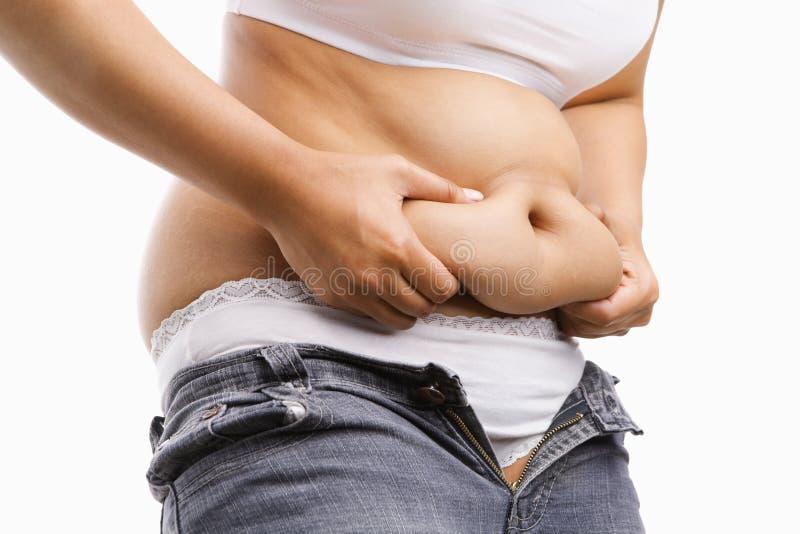 Fette Frau, die ihren fetten Bauch klemmt lizenzfreie stockfotografie