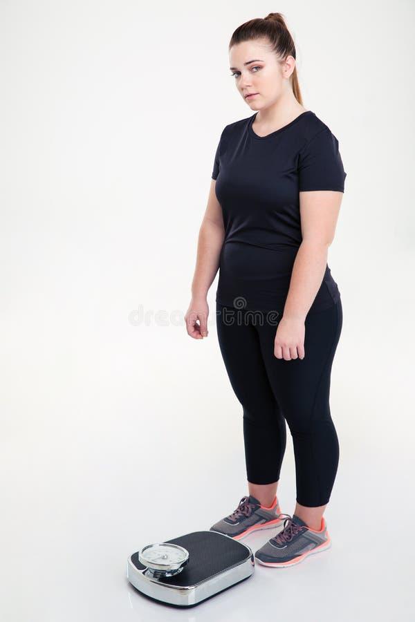 Fette Frau, die mit Waage steht lizenzfreies stockfoto