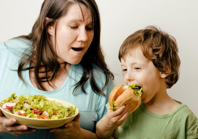 Fette Frau, die Salat und kleinen netten Jungen mit hält lizenzfreies stockbild