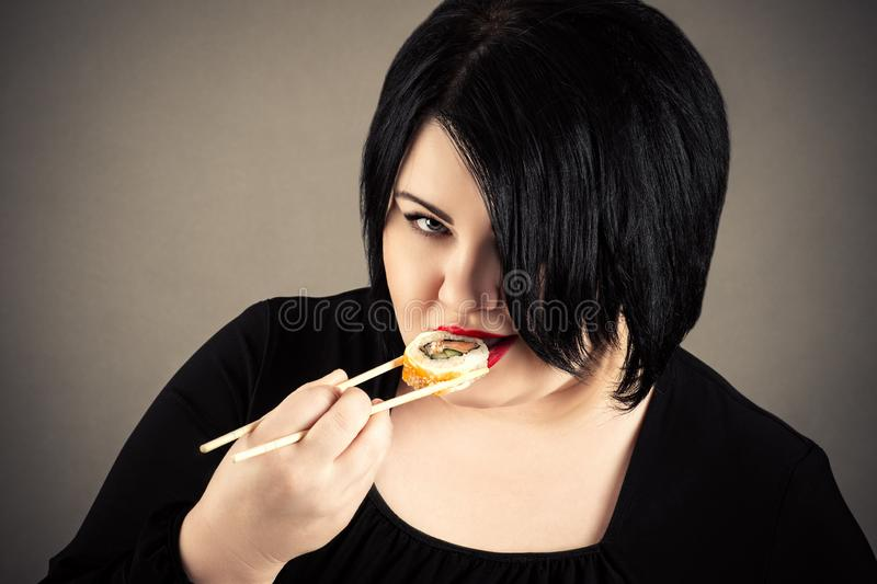 Fette Frau, die Sushi und Rollen isst lizenzfreie stockfotografie