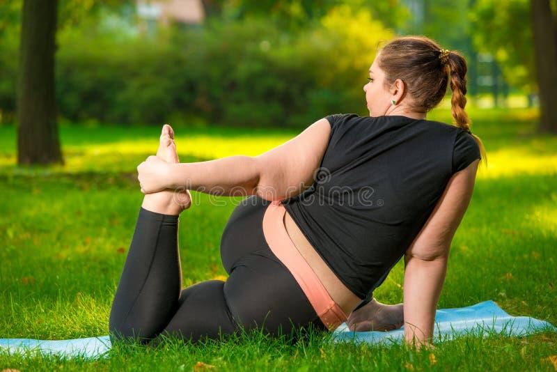 fette Frau im Park, der Yoga, Plusgrößenfrau tut, ist sehr flexibel lizenzfreie stockfotos