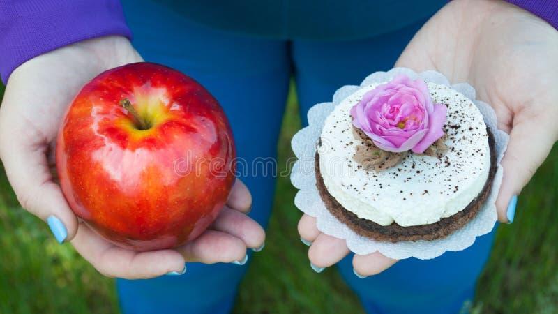 Fette Frau möchte Gewichtsdiät verlieren, die Draufsicht in der blauen Klage auf grünem Gras roten großen Apfel oder rundes Braun lizenzfreie stockfotos