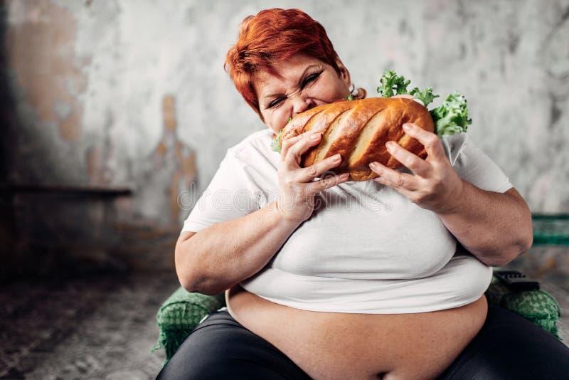 Fette Frau sitzt im Stuhl und isst das Sandwich, bulimisch stockbild