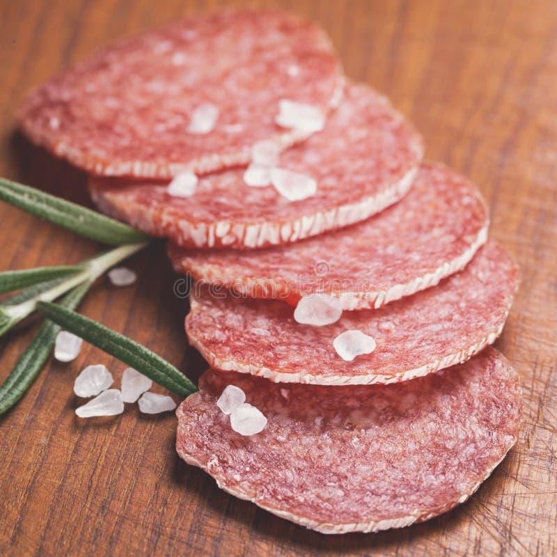 Fette italiane della salsiccia del salame con i rosmarini ed il sale marino fotografie stock