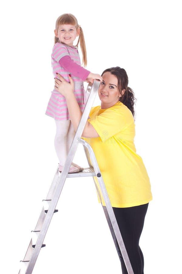 Fette Mutter und kleines Mädchen mit Strichleiter lizenzfreies stockfoto