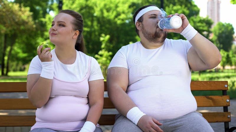 Fette Paare auf Bank, Trinkwasser des Mannes, Frau, die Apfel, gesunden Lebensstil isst stockfotografie