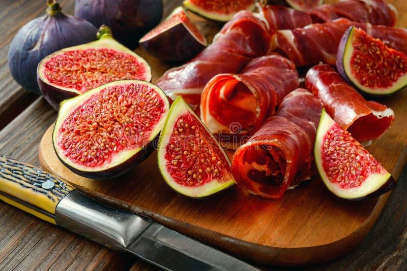 Fette secche del jamon con i fichi sulla tavola di legno immagini stock libere da diritti