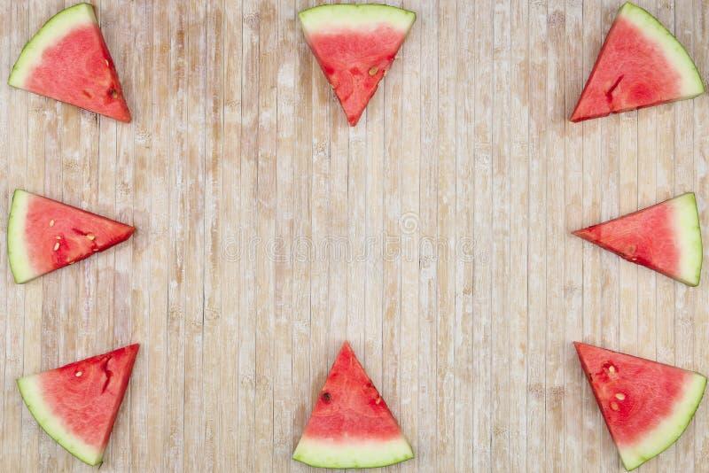 Fette triangolari di anguria che formano i giochi geometrici per lo spazio della copia su un fondo di legno leggero fotografie stock libere da diritti