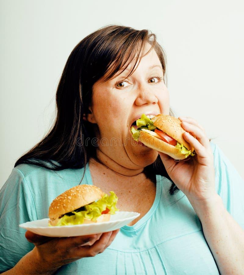 Fette weiße Frau, die Wahl zwischen dem Hamburger und Salat, emotionales ungesundes Lebensmittel essend, Lebensstilleutekonzept h stockfotos