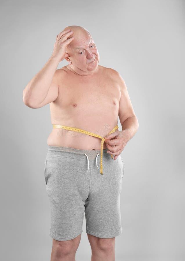 Fetter älterer Mann mit messendem Hahn stockbilder