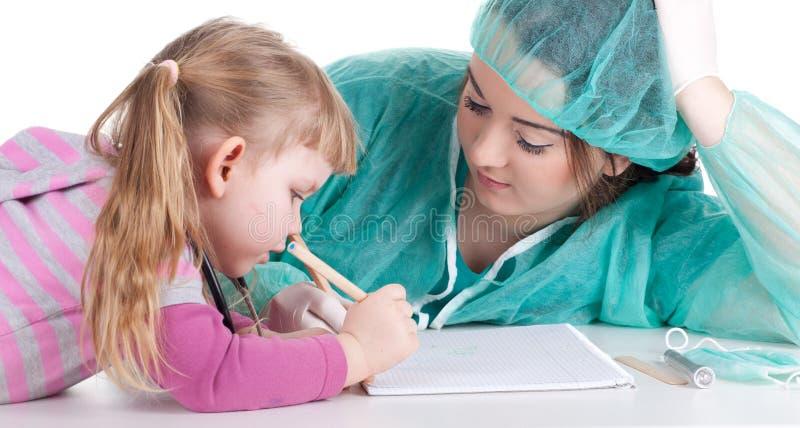 Fetter Frauendoktor mit kleinem Mädchen lizenzfreies stockbild