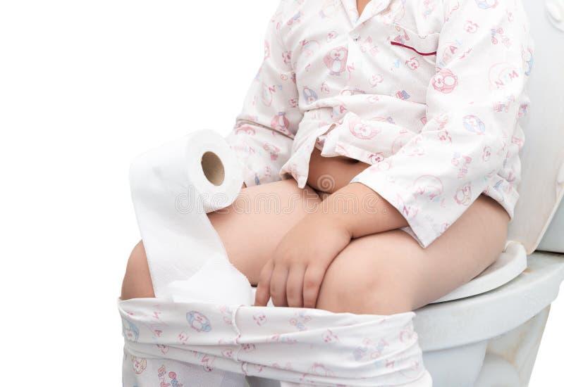 Fetter Junge, der auf der Toilette lokalisiert sitzt lizenzfreie stockfotografie