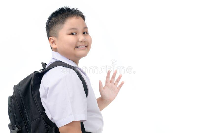 Fetter Jungenstudent, der zur Schule und zum Zum Abschied winken geht lizenzfreies stockfoto