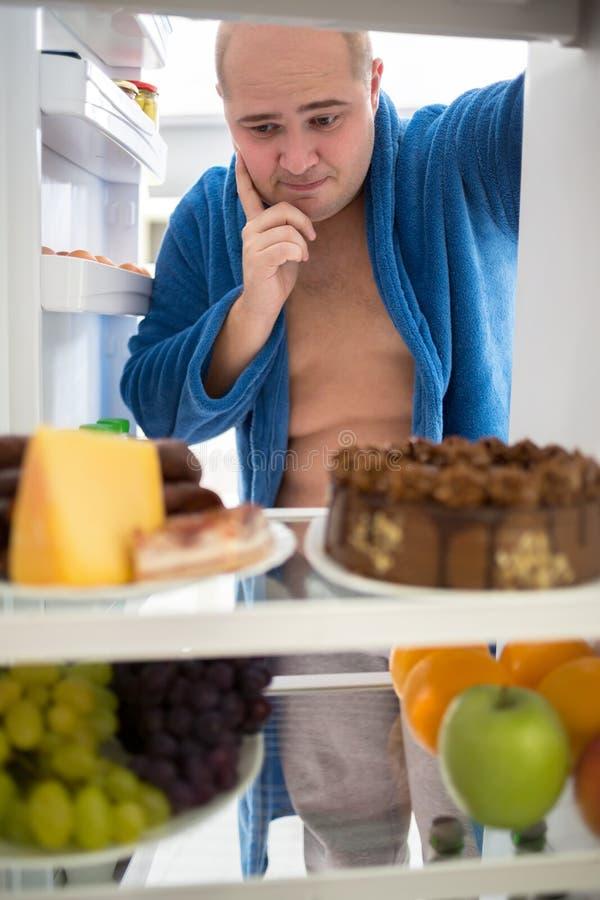 Fetter Kerl denken was, vom Kühlschrank zu essen stockfotografie