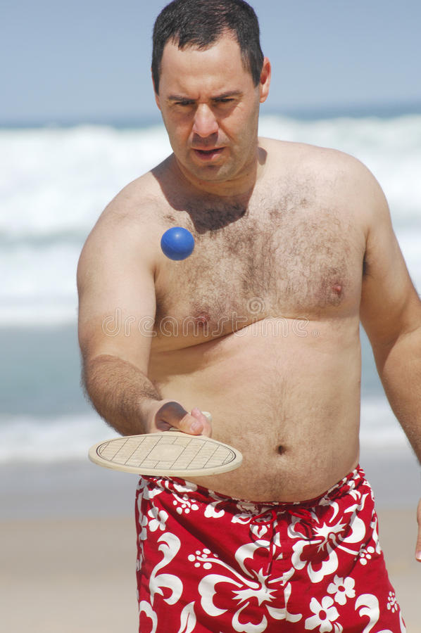 Fetter Mann, der Strandtennis spielt lizenzfreie stockbilder