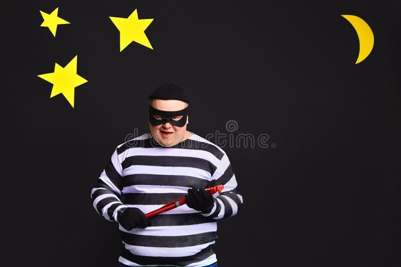 Fetter praller grausamer Einbrecher in einer Maske auf schwarzem Hintergrund stockfotografie