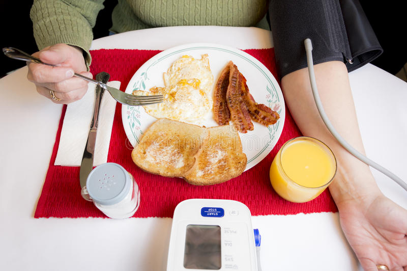Fetthaltiges Frühstück bei der Überwachung des Blutdruckes lizenzfreie stockfotos