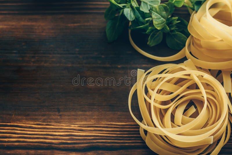 Fettuccine и базилик макаронных изделий на деревянной доске стоковое фото