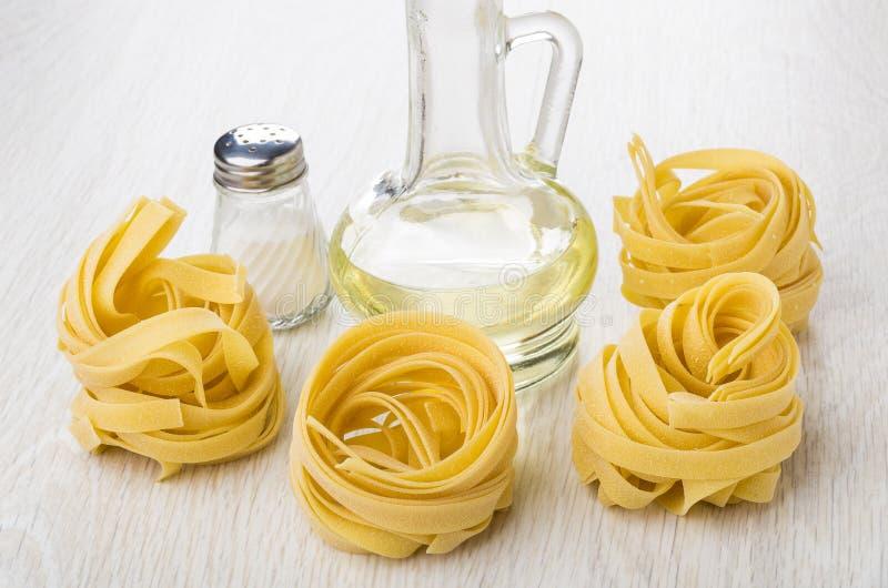 Fettuccine макаронных изделий, соль, бутылка постного масла на таблице стоковое изображение rf