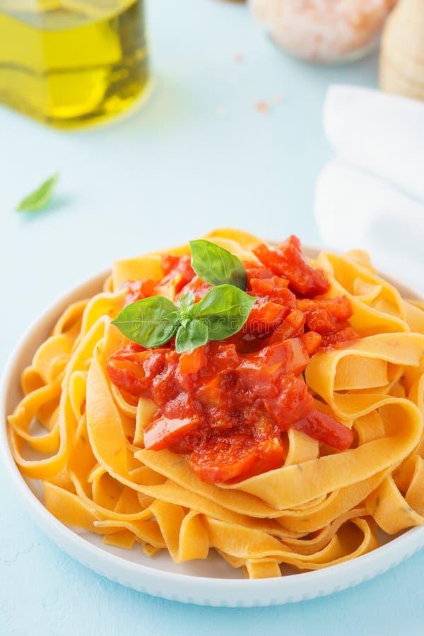 Fettuccine макаронных изделий с пряными томатным соусом, болгарскими перцами и базиликом стоковые фотографии rf