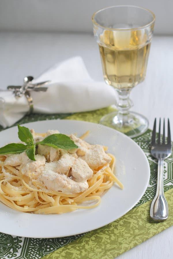 Fettuccine с цыпленком в сметанообразном соусе служил с бокалом вина стоковые изображения rf