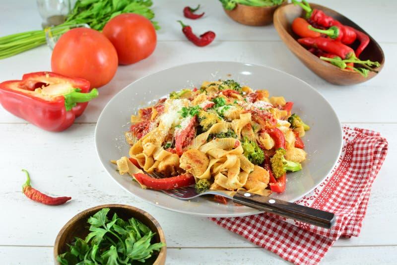 Fettuccine цыпленка с овощами на белой предпосылке стоковая фотография